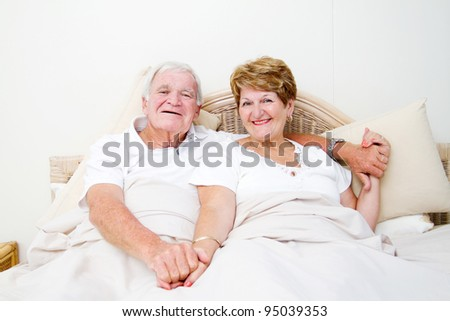 happy senior couple in bed relaxing - stock photo