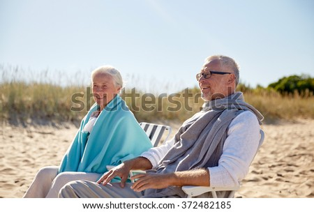 happy senior couple in chairs on summer beach - stock photo