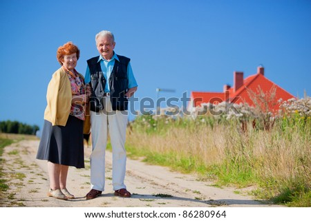 Happy senior couple in front of their house - stock photo