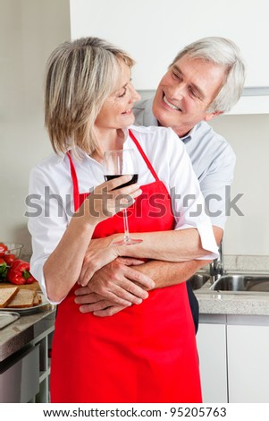 Happy senior couple in kitchen with glass of red wine - stock photo