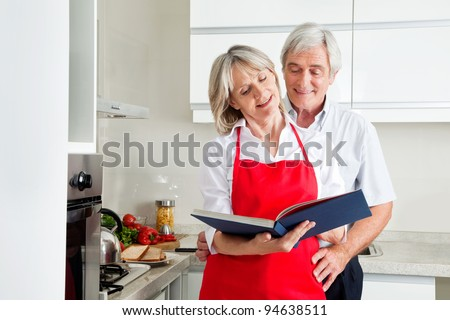 Happy senior couple in kitching looking for recipes in a cookbook - stock photo