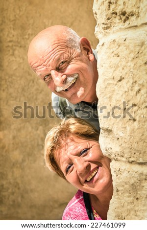 Happy senior couple in love during retirement - Joyful elderly lifestyle with man and woman with funny playful attitude - Visiting the old town during a sightseeing tour - stock photo