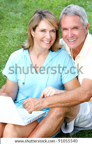 Happy senior couple in love in the park with laptop computer. - stock photo