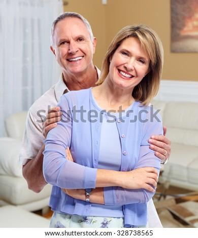 Happy senior couple in love over house background. - stock photo