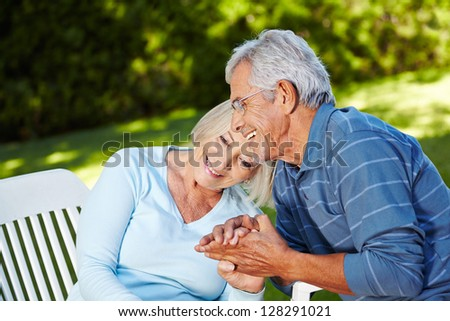 Happy senior couple in love sitting outside in a garden - stock photo