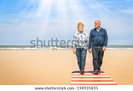 Happy senior couple in love walking hand in hand at the beach - Healthy and joyful elderly lifestyle with man and her wife spending time together outdoors in a sunny day - stock photo
