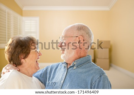 Happy Senior Couple In Room with Moving Boxes on the Floor. - stock photo
