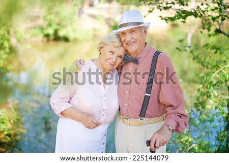 Happy senior couple in smart casual looking at camera in natural environment - stock photo