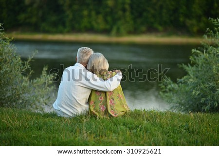 Happy senior couple  in summer near lake - stock photo