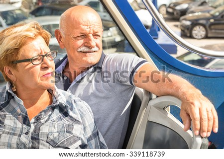 Happy senior couple in travel moment on sightseeing bus - Concept of active elderly during retirement - Wanderlust concept with mature people spending free time together - Sunny afternoon color tones - stock photo