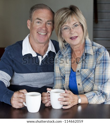 happy senior couple is having coffee together indoors - stock photo
