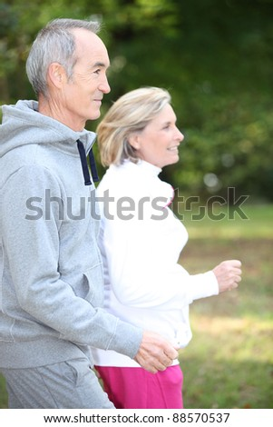Happy senior couple jogging - stock photo