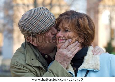 Happy senior couple kiss each other. - stock photo