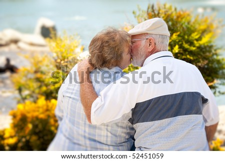 Happy Senior Couple Kissing Each Other in The Park. - stock photo