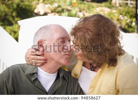 Happy Senior Couple Kissing in the Park. - stock photo