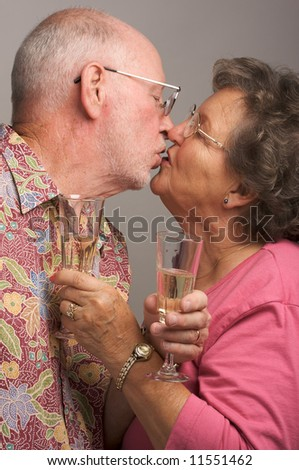Happy Senior Couple Kissing while holding Champagne glasses. - stock photo