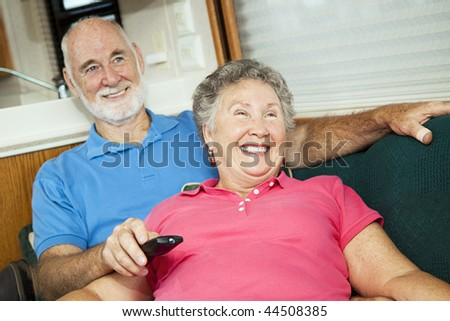 Happy senior couple laughing as they watch TV together in their motor home. - stock photo