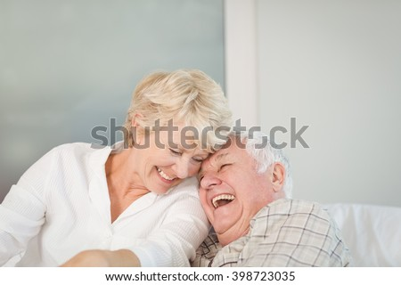 Happy senior couple laughing in bed at home - stock photo