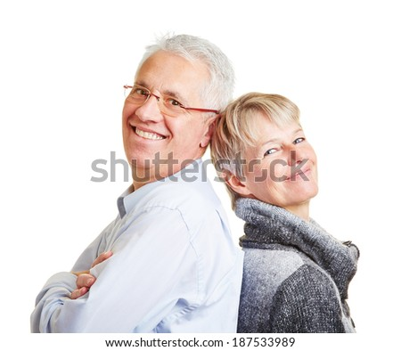 Happy senior couple leaning on each other back to back - stock photo