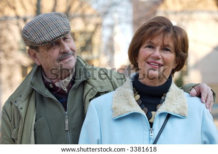 Happy senior couple look at the camera. Selective focus is placed on the women while the man behind her is slightly out of focus. - stock photo