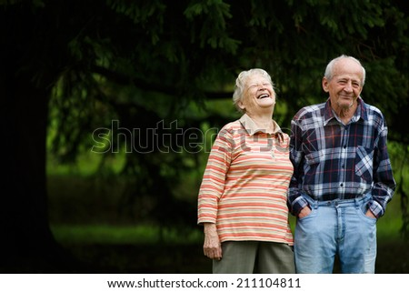 Happy senior couple looking at camera and laughing, Senior woman hugging her partner on a sunny day, Smiling Caucasian older couple embracing - stock photo