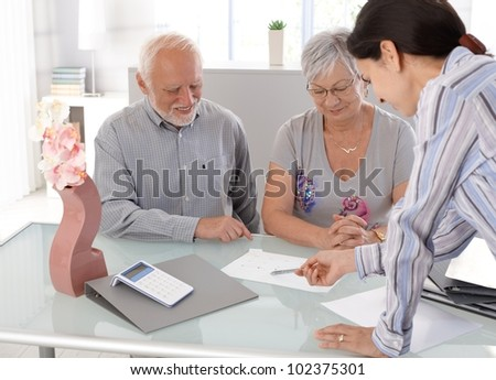 Happy senior couple looking at chart at financial advisor. - stock photo