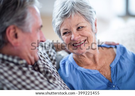 Happy senior couple looking at each other and smiling at home - stock photo
