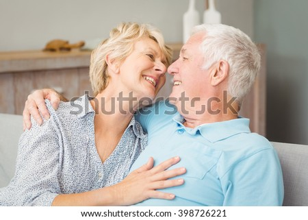 Happy senior couple looking at eachother while hugging at home