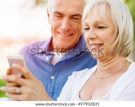 Happy senior couple looking at smartphone