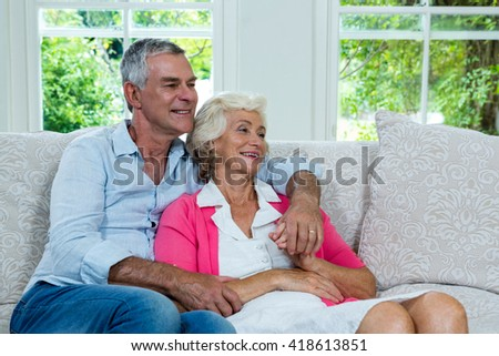 Happy senior couple looking away at home - stock photo