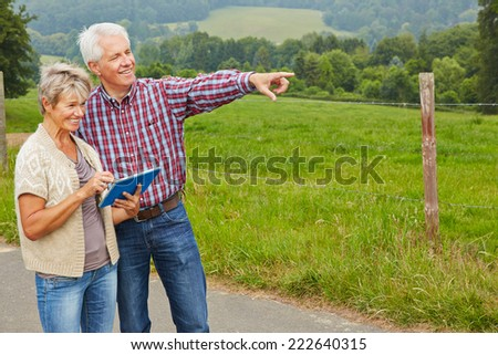 Happy senior couple looking for directions with tablet computer while hiking - stock photo