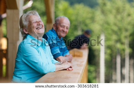 Happy senior couple looking to surroundings areas and smiling. Posing in wooden tower and watching for nature scenery in forest. Summer holidays. Blurred forest background. - stock photo