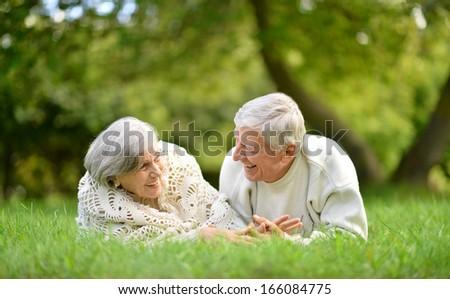 Happy senior couple lying in summer park - stock photo