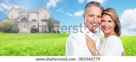 Happy senior couple near family house. - stock photo