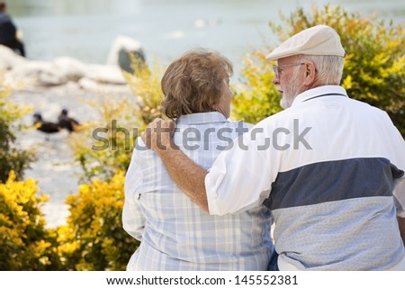 Happy Senior Couple on a Bench Enjoying Each Other in The Park. - stock photo