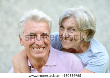 Happy senior couple on a gray background