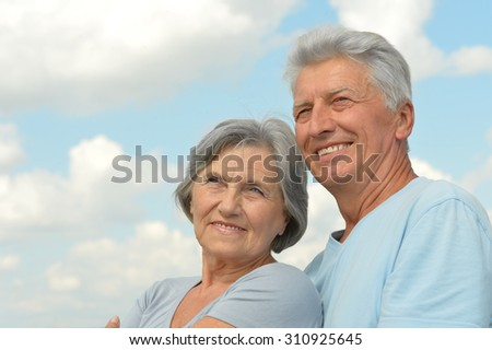 Happy senior couple on a sky background - stock photo