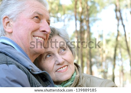 happy senior couple on a walk in the forest in the spring - stock photo