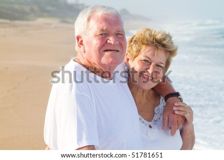 happy senior couple on beach - stock photo