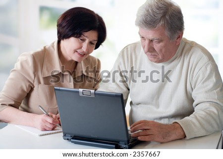 "Happy senior couple on laptop. Concept may be is ""home office"" or ""shopping in internet shop""."