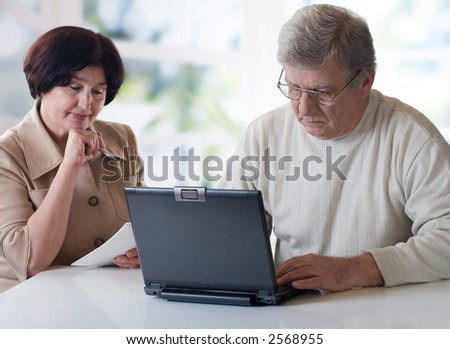 "Happy senior couple on laptop. Concept may be is ""home office"" or ""shopping in internet shop"". Focus on man."