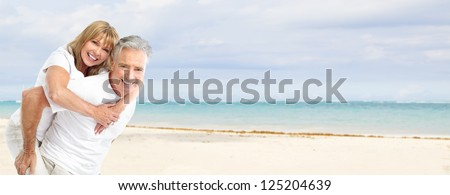 Happy senior couple on the beach. Exotic luxury resort. - stock photo