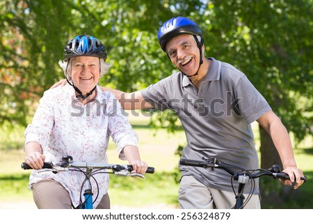 Happy senior couple on their bike on a sunny day - stock photo