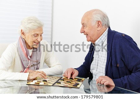 Happy senior couple playing checkers together in a retirement home - stock photo