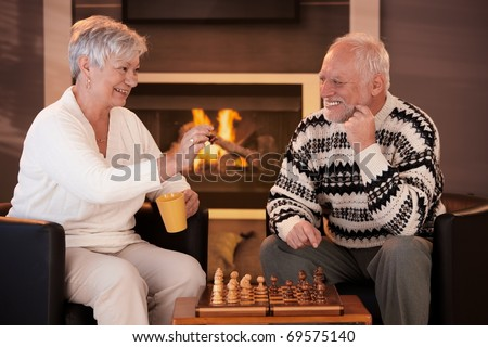 Happy senior couple playing chess at home, drinking tea in front of fireplace, on winter night, laughing.? - stock photo