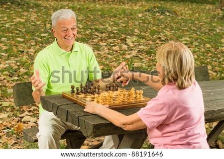 Happy senior couple playing chess on a park bench. - stock photo