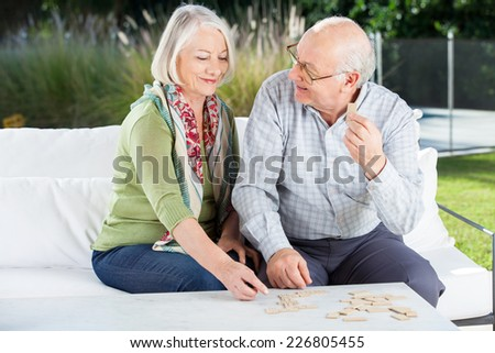 Happy senior couple playing dominoes while sitting on couch at nursing home porch - stock photo