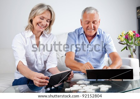 Happy senior couple playing rummy together at home. - stock photo