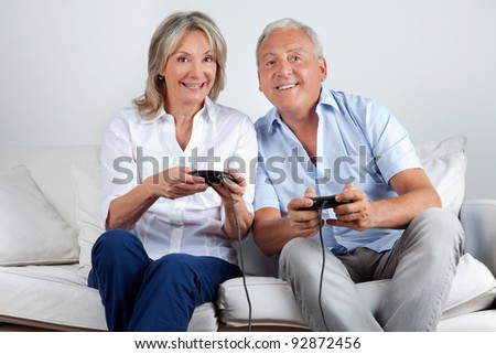 Happy senior couple playing video game at home - stock photo