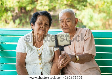 Happy senior couple posing for a selfie at home - stock photo